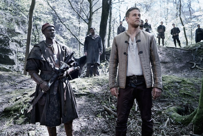 Djimon Hounsou as Bedivere and Charlie Hunnam as Arthur in a scene filmed in Seven Sisters Wood, Forest of Dean. © 2017 Warner Bros. Entertainment, Inc. All rights reserved