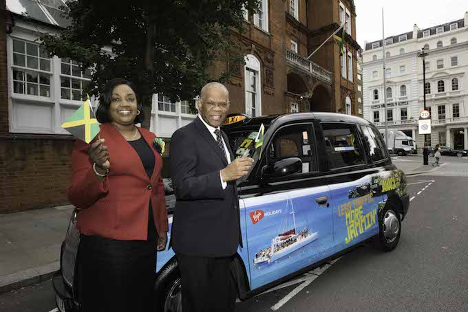 Deputy High Commissioner Angela Rose Howell and His Excellency Seth George Ramocan, Jamaican High Commissioner to the UK, with one of the Jamaica wrapped taxis outside the Jamaican High Commission in London